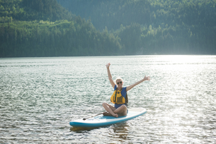 Excited young woman sitting on paddleboard in lakeの写真素材 [FYI02238232]