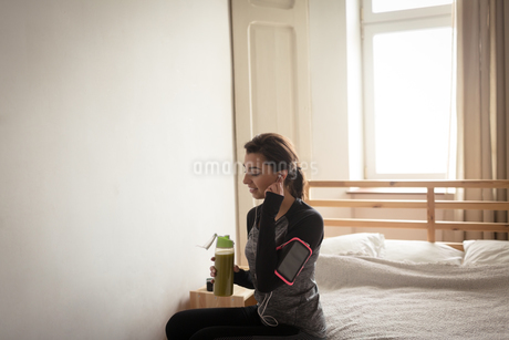 Woman holding bottle while sitting on bedの写真素材 [FYI02238291]