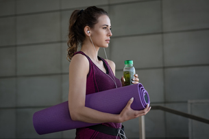 Woman with exercise mat and water bottle at fitness studioの写真素材 [FYI02238309]