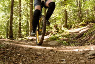 Low section of woman riding unicycle on trailの写真素材 [FYI02238326]