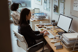 Female executive working on computer at deskの写真素材 [FYI02238334]