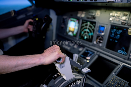 Cropped hands of male pilot pushing lever in cockpitの写真素材 [FYI02238354]