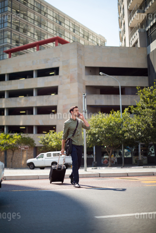 Man walking with suitcase while talking on mobile phoneの写真素材 [FYI02238356]