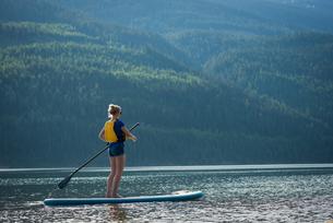 Young woman paddleboarding in lakeの写真素材 [FYI02238393]