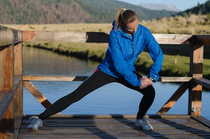 Young female athlete stretching while exercising by lakeの写真素材 [FYI02238394]