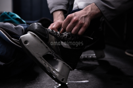 Low section of player tying ice skateの写真素材 [FYI02238396]