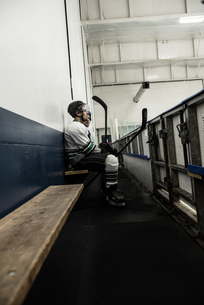 Ice hockey player with teammate on seat at corridorの写真素材 [FYI02238432]