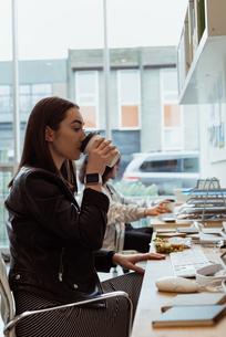 Female executive having coffee at deskの写真素材 [FYI02238458]
