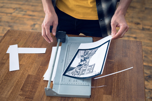 Mid section of photographer cutting photograph on paper cutting toolの写真素材 [FYI02238460]