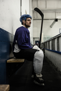 Thoughtful hockey player on seat at corridorの写真素材 [FYI02238468]