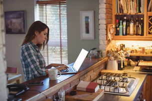 Woman using laptop in kitchen at homeの写真素材 [FYI02238484]