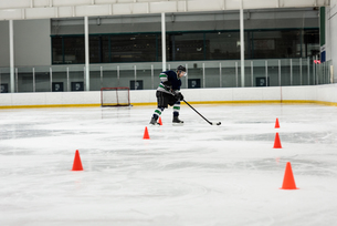 Ice hockey player practicing drills at rinkの写真素材 [FYI02238503]