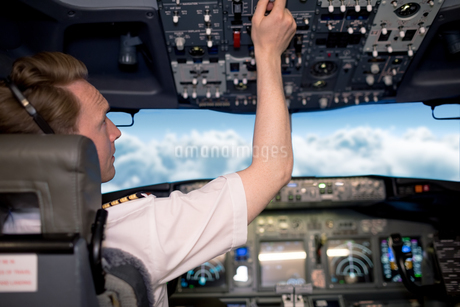 Young male pilot switching controls in cockpitの写真素材 [FYI02238523]