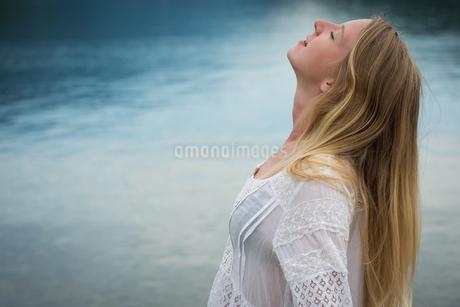 Profile view of woman at lakeshoreの写真素材 [FYI02238532]