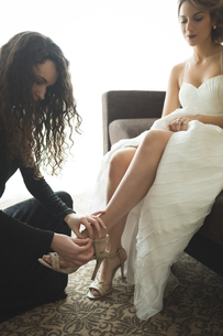 Bridesmaid helping bride to put on wedding shoesの写真素材 [FYI02238541]