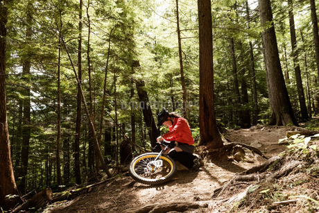 Woman adjusting unicycle while sitting on trailの写真素材 [FYI02238545]