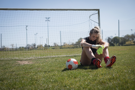 Tired soccer player sitting on fieldの写真素材 [FYI02238549]