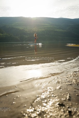 Distant view of young woman paddleboarding in lakeの写真素材 [FYI02238585]