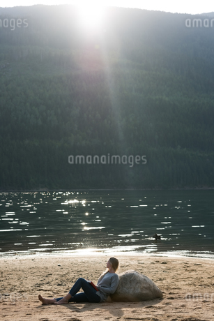Side view of woman sitting with novel at lakeshoreの写真素材 [FYI02238595]