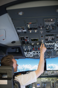 Rear view of male pilot switching controls in air vehicleの写真素材 [FYI02238625]