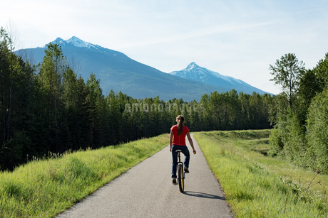 Rear view of woman riding unicycle on roadの写真素材 [FYI02238627]