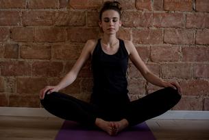 Woman performing yoga in fitness studioの写真素材 [FYI02238646]