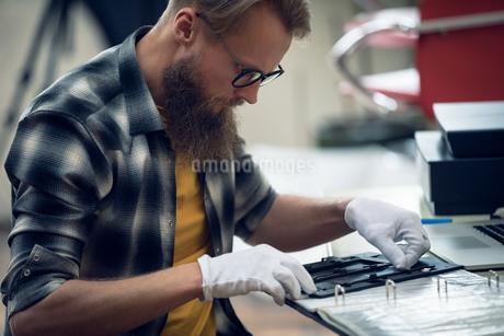 Photographer adjusting negatives in frameの写真素材 [FYI02238647]