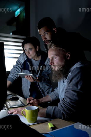 Colleagues working on personal computer at deskの写真素材 [FYI02238656]