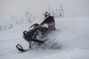 Man riding snowmobile in snowy alpsの写真素材 [FYI02238712]