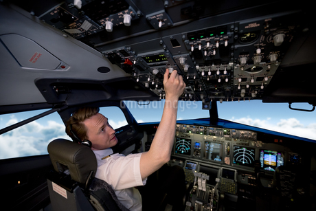 Handsome young pilot switching controls in cockpitの写真素材 [FYI02238720]