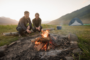 Couple preparing sausage on campfire at campsiteの写真素材 [FYI02238722]