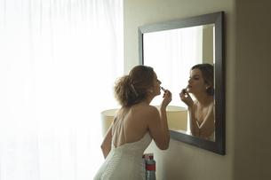 Bride applying her makeup doing her wedding preparationの写真素材 [FYI02238729]