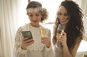 Bride and bridesmaid using mobile phone while having champagneの写真素材 [FYI02238735]
