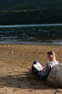 Rear view of woman sitting on sand reading novelの写真素材 [FYI02238741]