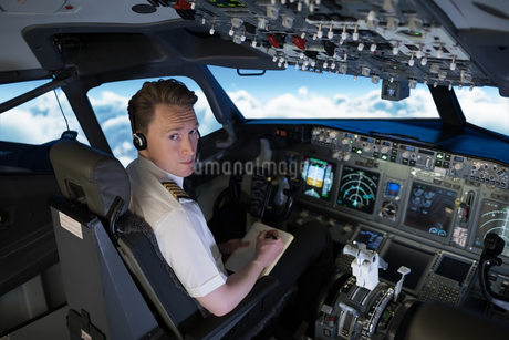 Confident young pilot writing on book while sitting in cockpitの写真素材 [FYI02238765]