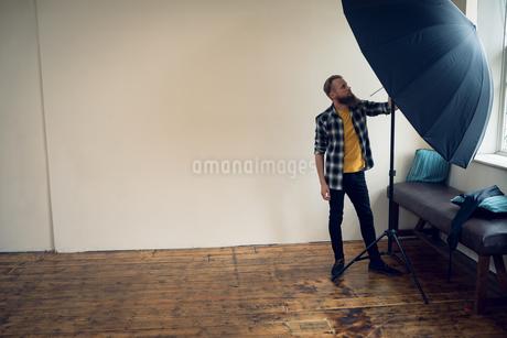 Full length of photographer adjusting umbrellaの写真素材 [FYI02238772]
