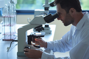 University student doing experiment on microscope in laboratoryの写真素材 [FYI02238774]