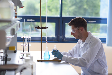 Side view of male college student practicing chemistry experimentの写真素材 [FYI02238781]