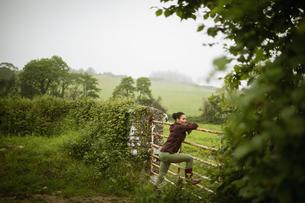 Woman leaning on rusty gateの写真素材 [FYI02238782]