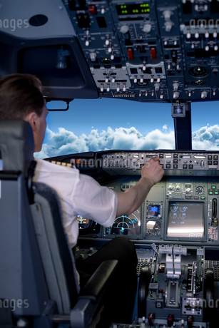 Young male pilot switching controls in air vehicleの写真素材 [FYI02238798]
