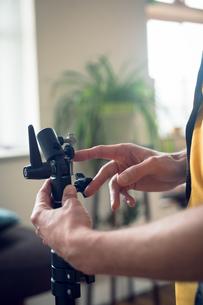 Cropped hand of photographer adjusting equipmentの写真素材 [FYI02238811]