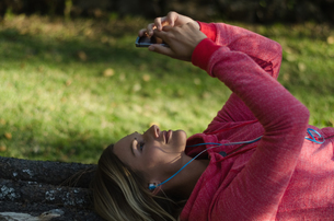 Close up of female hiker using phone while lying on retaining wallの写真素材 [FYI02238827]