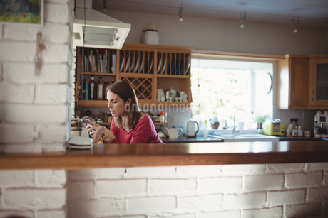 Woman using mobile phone in kitchenの写真素材 [FYI02238885]