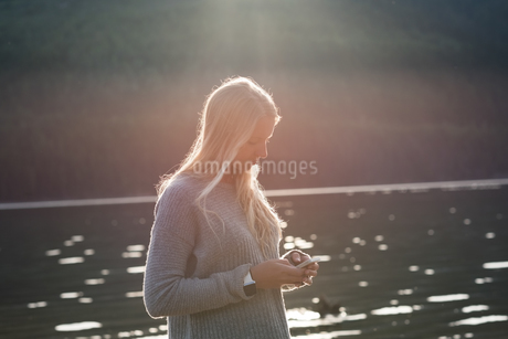 Young woman text messaging from mobile phoneの写真素材 [FYI02238890]