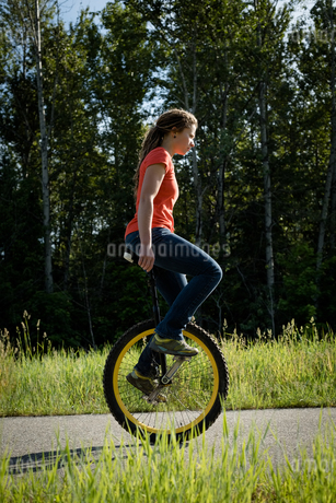 Side view of woman unicycling on roadの写真素材 [FYI02238917]