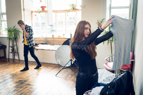 Woman holding t shirt while working in studioの写真素材 [FYI02238944]