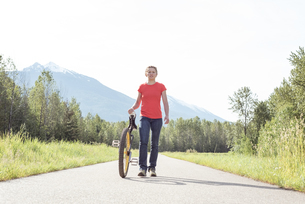 Young woman walking with unicycle on roadの写真素材 [FYI02238946]