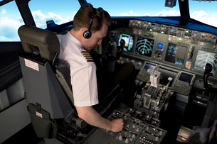 High angle view of young male pilot switching control while sitting in cockpitの写真素材 [FYI02238963]