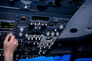 Cropped hand of male pilot switching control in cockpitの写真素材 [FYI02239023]