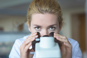University student doing experiment on microscope in laboratoryの写真素材 [FYI02239028]